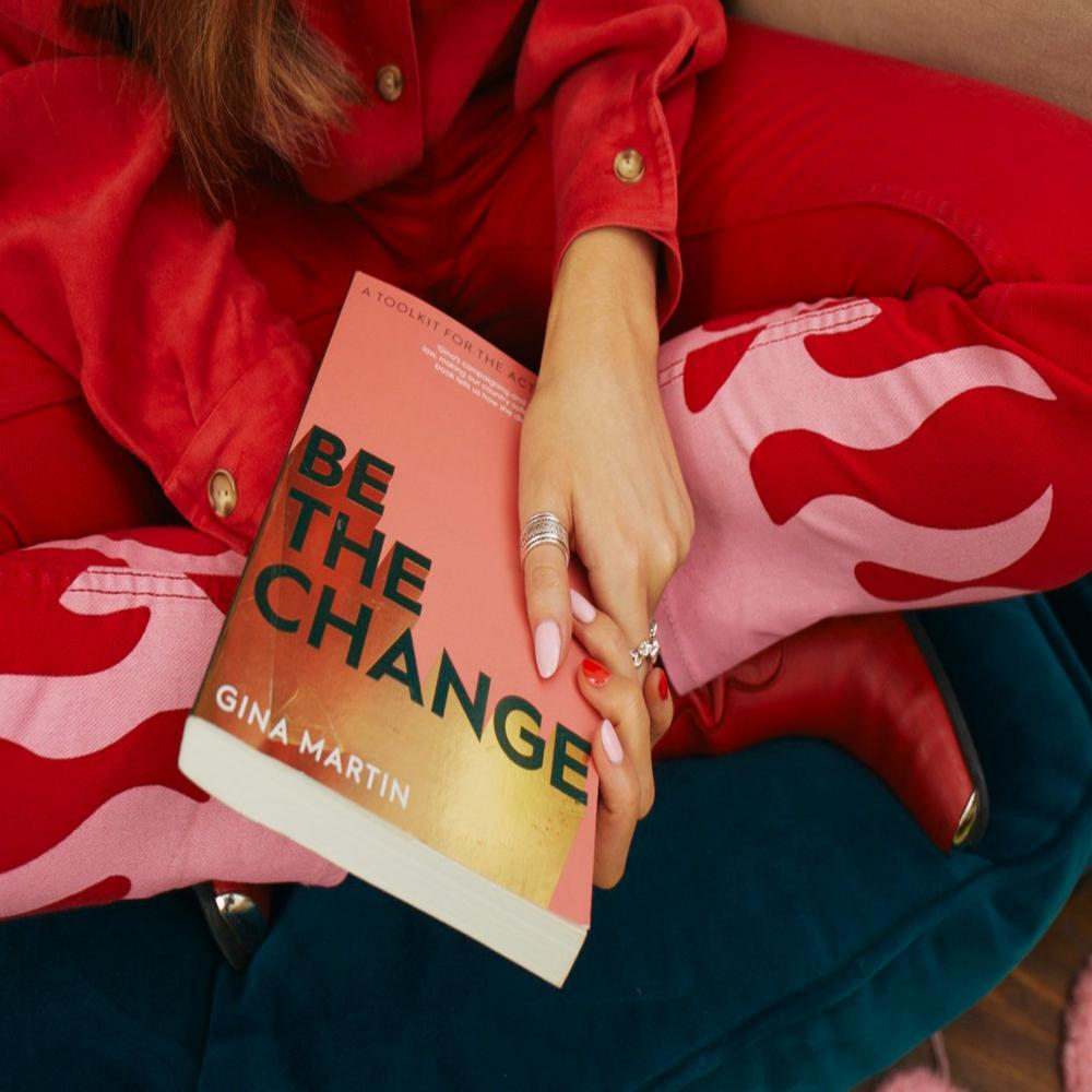 Woman holding book that reads 'be the change' on the cover